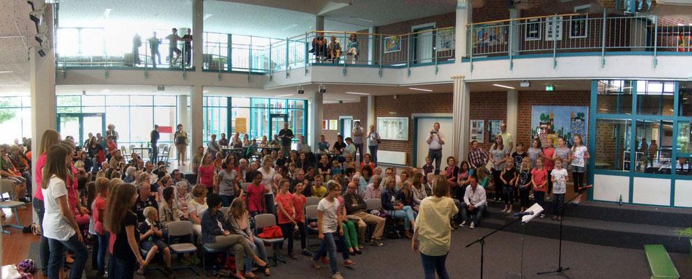 Eine voll besetzte Aula in der Wolfhelmschule wartet auf die jungen Sängerinnen und Sänger