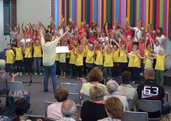 Begeisterte Kinder singen mit viel Bewegung und Freude