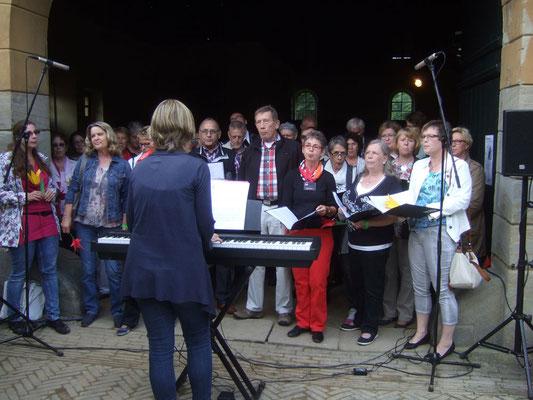 Die Sängerinnen und Sänger mit ihrer Chorleiterin Sigrid Hartmann im Torbogen