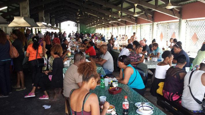 Geschäftsleute, Hausfrauen und Touristen sitzen hier an langen Tischen zusammen.