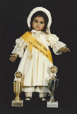 "Erster Platz Gold, der Jury GDS Weltpuppenkongress Heidelberg 1988, Kategorie ""Farbige Reproduktionen"" sowie erster Preis Puplikumspreis."