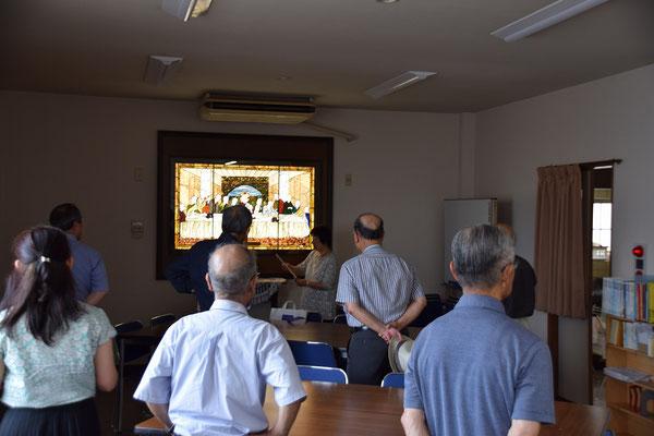 集会室で、旭東教会の学芸員、光代さんがステンドグラスの解説を開始。