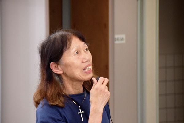 み言葉カフェのリーダーのおひとり、安佐子さん 開始時間を高い所にある時計を見ながらお知らせ中の一枚