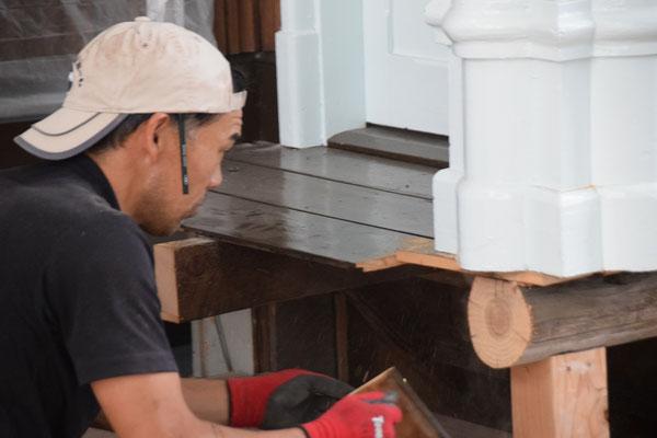 2020年5月12日(火)主任大工さん 講壇と柱をの支え木をに手動でノコギリを入れて次の作業に備えます。