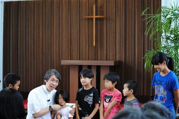 夏のファミリー礼拝の報告時に、森牧師は参加してくれた子どもたちにインタビュー中。お名前と学校と、いつも何して遊んでいるかな?
