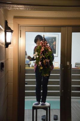 2016年11月、アドヴェントを目前にして、夜遅くに教会玄関に手製のスワッグをセッティングする美樹さん。