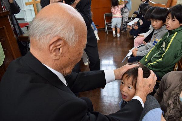 2015年11月の子ども祝福礼拝のひとこま おおきいおじいちゃんである寿先生からの祝福を受けるの図