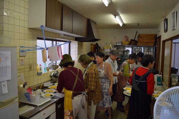 大忙しの台所。10日程前にご主人を天に送られた艶子さんも帽子を被って奉仕されています。