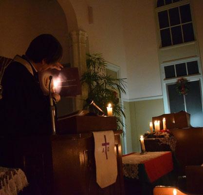 クリスマスイヴ燭火で子どもたちの姿を確認して、絵本を読む森牧師
