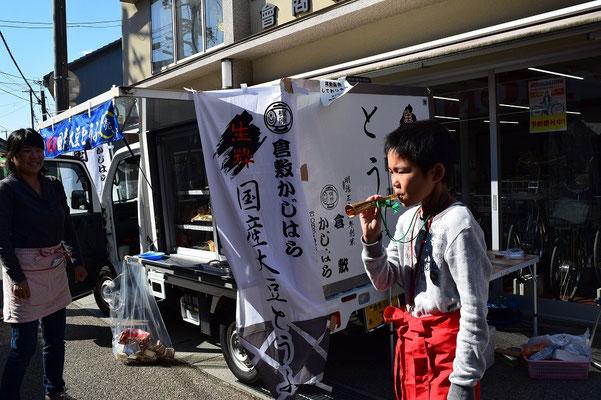 【西大寺の町並みシリーズ(その54 )】2015年11月3日の文化の日、五福通りのお祭りで倉敷かじはら豆腐店のぼくちゃんが一生懸命にお手伝い。左にはお母さん。とにかく美しい時間でした。