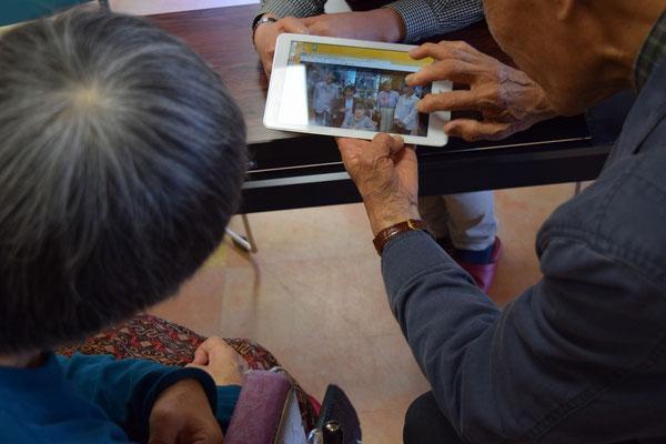 ほぼ一年前の幸子さんの姿も見えるホームページの写真をタブレットで正さんが紹介。