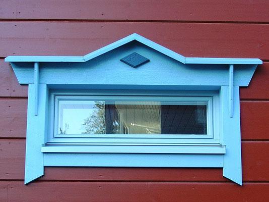 Buntes Blockhaus - Holzhaus mit blauen Fensterrahmen