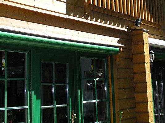 Rundbohlenhaus mit grünen Rolllädenkästen
