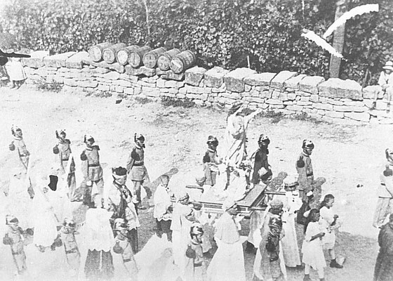 Anni '30, processione dell'Assunta a Vigo Meano. Degno di nota l'abbigliamento dei coscritti che portano la statua della Madonna: tunica bianca, mantella e berretto azzurri. Seguivano i pompieri. Sul muro i barili di barite