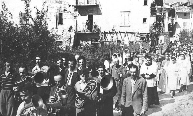 """Anni '40. Processione in onore di Sant'Antonio. Si riconoscono da sx: Mario Franceschini, il """"Baffo"""" ed Egidio Bortolotti. Sullo sfondo casa Gottardi. Da Silvano Franceschini"""