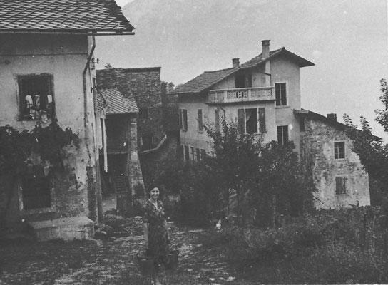 """Veduta di Gardolo di Mezzo, lungo la via Castel di Gardolo. A destra si nota """"Palazzo Sontacchi"""" oggi casa Merzi, sullo sfondo casa Tessadri, 1930. Da Luciano Tessadri"""