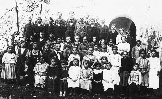 Scolaresca mista della Scuola Elementare di Vigo Meano. Si riconoscono i maestri L.Leonardi e Candido Andreolli, 1918. Da Archivio Scuola Elementare di Vigo Meano.