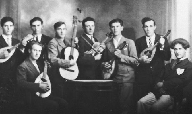 Rappresenta il secondo gruppo mandolinistico di Meano, attivo fra la fine degli anni '20 e la fine degli anni '30. Fu scattata nello studio di Silvio Pedrotti, fotografo e fondatore, coi fratelli, del coro della SAT, verso il 1930-'32. Da Evaristo Lessi