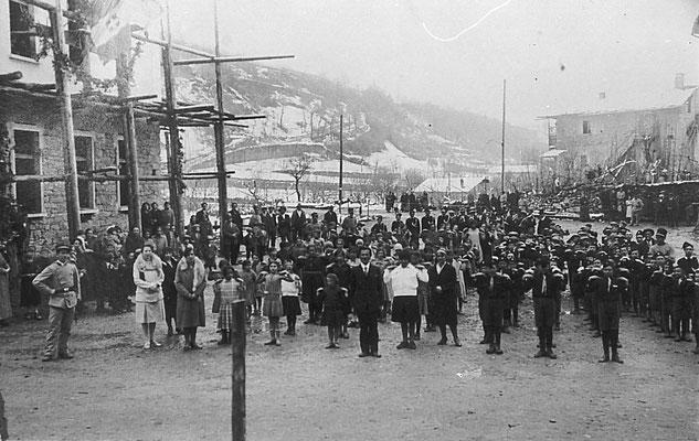 1931, Vigo Meano. Saggio ginnico di fine anno scolastico. A sinistra la maestra Tomasi, al centro il maestro Leonardi. Serie di esibizioni ginniche nella piazza alla presenza delle autorità locali. Dall'archivio delle scuole elementari di Vigo Meano.