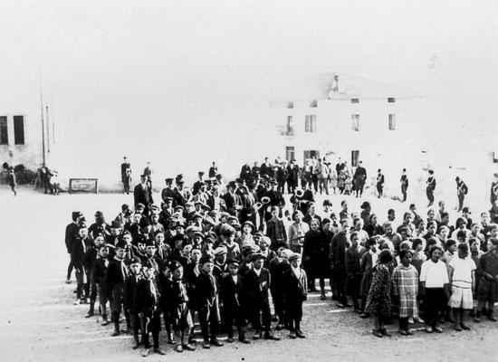 1931, Vigo Meano. Saggio ginnico di fine anno scolastico.  Serie di esibizioni ginniche nella piazza alla presenza delle autorità locali. Dall'archivio delle scuole elementari di Vigo Meano.