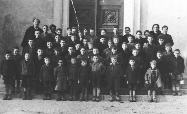 Classe elementare di Vigo Meano davanti a portale della chiesa, con maestro Leonardi e maestra Alma Zulian, 1945. Da Ivana da Mattivi Edoardo