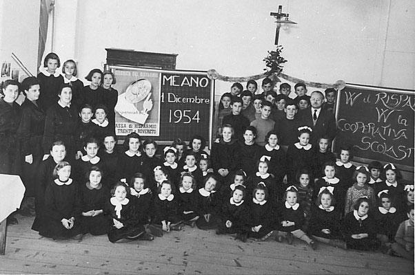 Il maestro Cacciari di Lavis (a destra nella foto) ebbe l'idea di organizzare, nei primi anni '50, una cooperativa scolastica: i ragazzi della IV classe (maschi e femmine, con mansioni diverse) dovevano lavorare un campo a vigna, 1954. Da Rosina Pilati.
