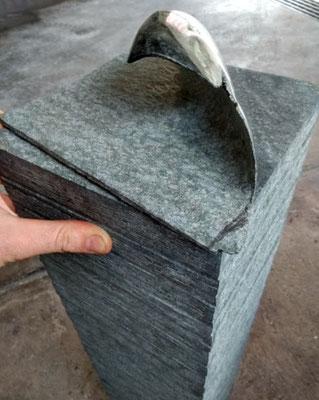 Grabstein aus Diabas mit sich ablösendem Blatt.