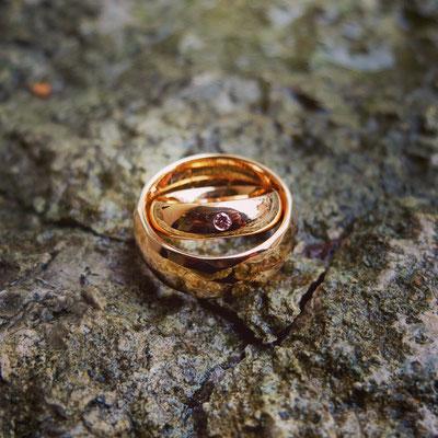 Trauringe in Gelbgold 750 mit einem pinken Diamanten im Damenring