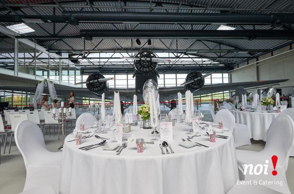 Viele gedeckte Tische befinden sich in einem Flugzeughangar neben einer JU 52. © noi! Event & Catering CmbH & Co. KG