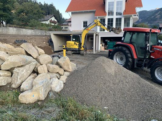 Bagger und Traktor beim errichten einer Stützwand aus Naturstein in Beton Mölltal Oberkärnten