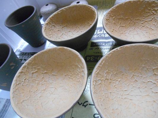 ご飯茶わんの内側に黄と白の化粧泥。湯飲みの外側に黒泥を塗り、黄泥でビックリを描く。