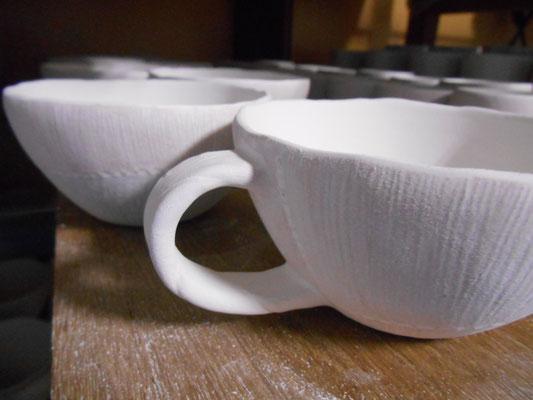 カップの内側に釉薬を柄杓掛けした後、フチからはみ出した釉薬を擦り落とし、取っ手部分を釉薬に浸し掛け