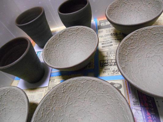 ご飯茶わんの内側に緑と白の化粧泥。湯飲みの外側に黒泥を塗るところまで。