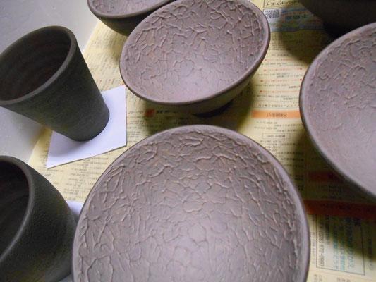 ご飯茶わんの内側に紫と白の化粧泥。湯飲みの外側に黒泥を塗るところまで。
