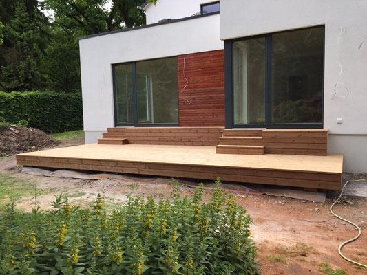 Als besonderes i-Tüpfelches erhielt das Haus eine einladenen Holzterrasse, die mit Holzstufen an das Fundament angepasst wurde.