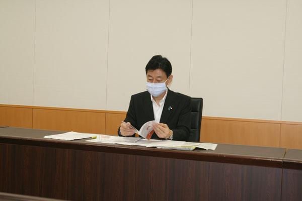 手渡したケアラー手帳に見入る西村大臣