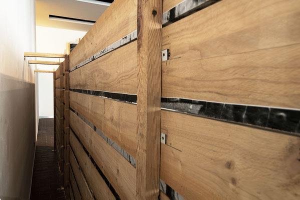 Mémorial Retirada 1 (vue arrière), images photographiques marouflées sur planches de bois brut, ossature bois. Le passage entre le mur et le dos de l'oeuvre est possible mais rendu volontairement contraignant.