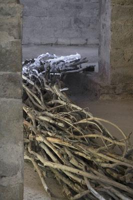 Coulée sèche, zoom est-ouest sur l'installation traversant les chapelles du collatéral nord, bois tressé, impressions laser et papier marouflés sur bois, lumière noire.