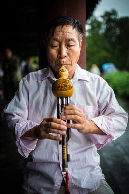 Portrait eines Mannes mit einer  Chinesische Hu-Lu-Si-Flöte