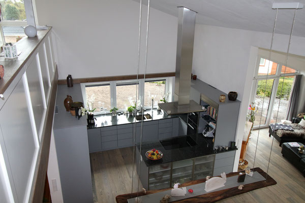 Ansicht von der Galerie auf die Küche, im Vordergrund eine Holzbohle als Hängelampe