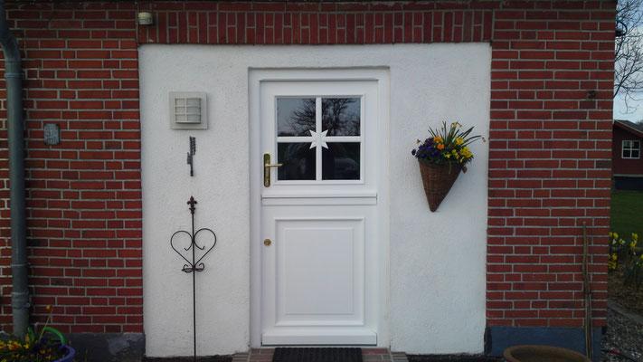 Haustür in Mahagoni als Klöntür in Rahmenbauweise mit unterer Füllung und oberer Verglasung mit  Sprossen im Sönke- Nissen- Koog- Stil, angeschlagen mit vier Sassba- Bändern, Türschloß: GU als Klöntürv