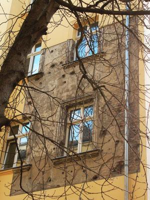 In einem renovierten Innenhof in Berlin ist eine Fläche belassen worden, um die Zerstörungen durch den Krieg nicht vergessen zu lassen