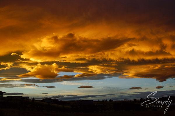 Tekapo, rot-goldiger Sonnenuntergang mit blauem Strich am Horizont