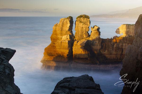 Punakaiki Pancake Rocks, Sonnenuntergang mit rötlich beleuchteten Felsen in der Meeresbrandung
