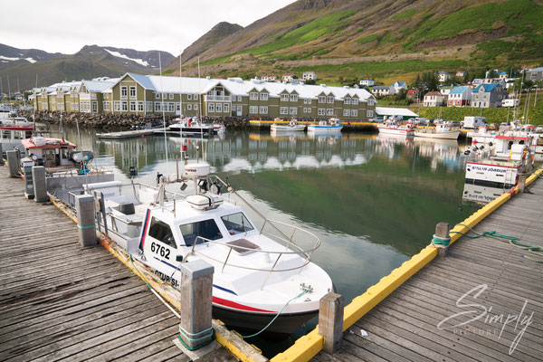 Boots-Steg mit einigen Booten und dem Hotel im Hintergung in Dalvík.