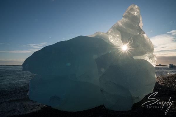 Grosse Eisscholle an der Jökulsárlón Glacier Lagoon mit der Sonne im Loch.