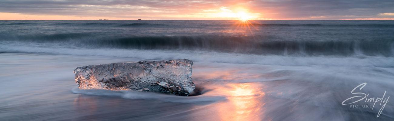 Sonnenuntergang mit einer schimmernden Eisscholle am Diamond Beach bei dem Jökulsárlón Glacier Lagoon.