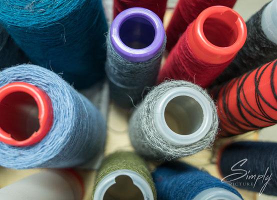 Rote, violette, graue, blaue Wollen-Fäden-Rollen in einer der vielen isländischen Manufakturen.