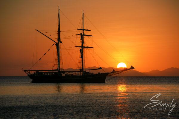 Queensland, Whitsundays, Segelschiffe auf dem Meer bei Sonnenuntergangsstimmung, roter Himmel