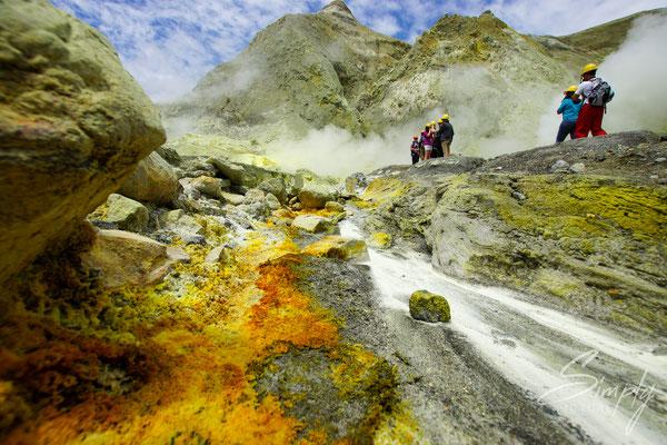 Whakaari, White Island, gelb-braun-rote Gesteine neben dem Weg mit Personen im Hintergund